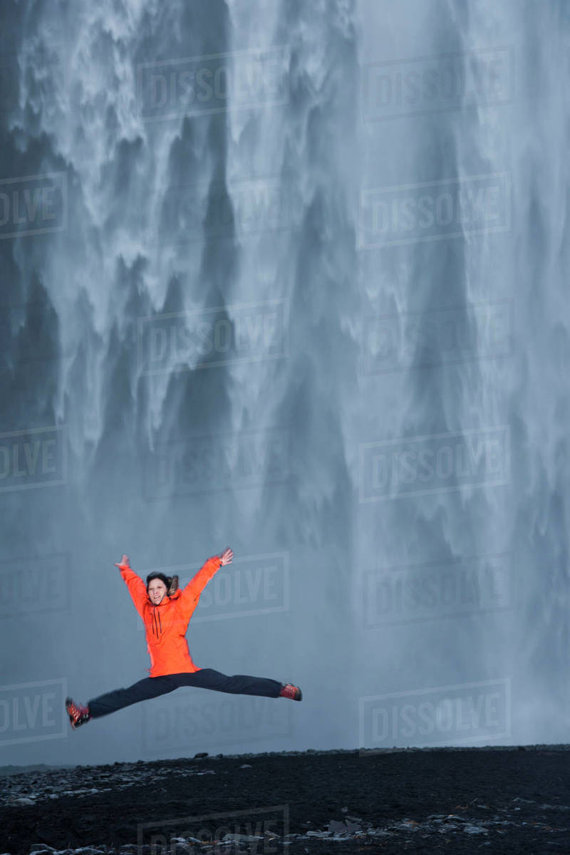 Woman jumping in front of  Skógafoss waterfall in south Iceland Royalty-free stock photo