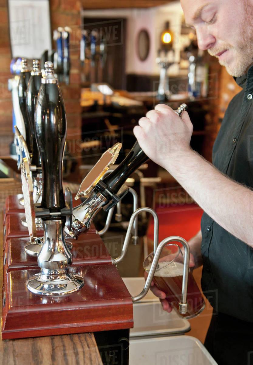 Bartender pulling beer at British pub Royalty-free stock photo