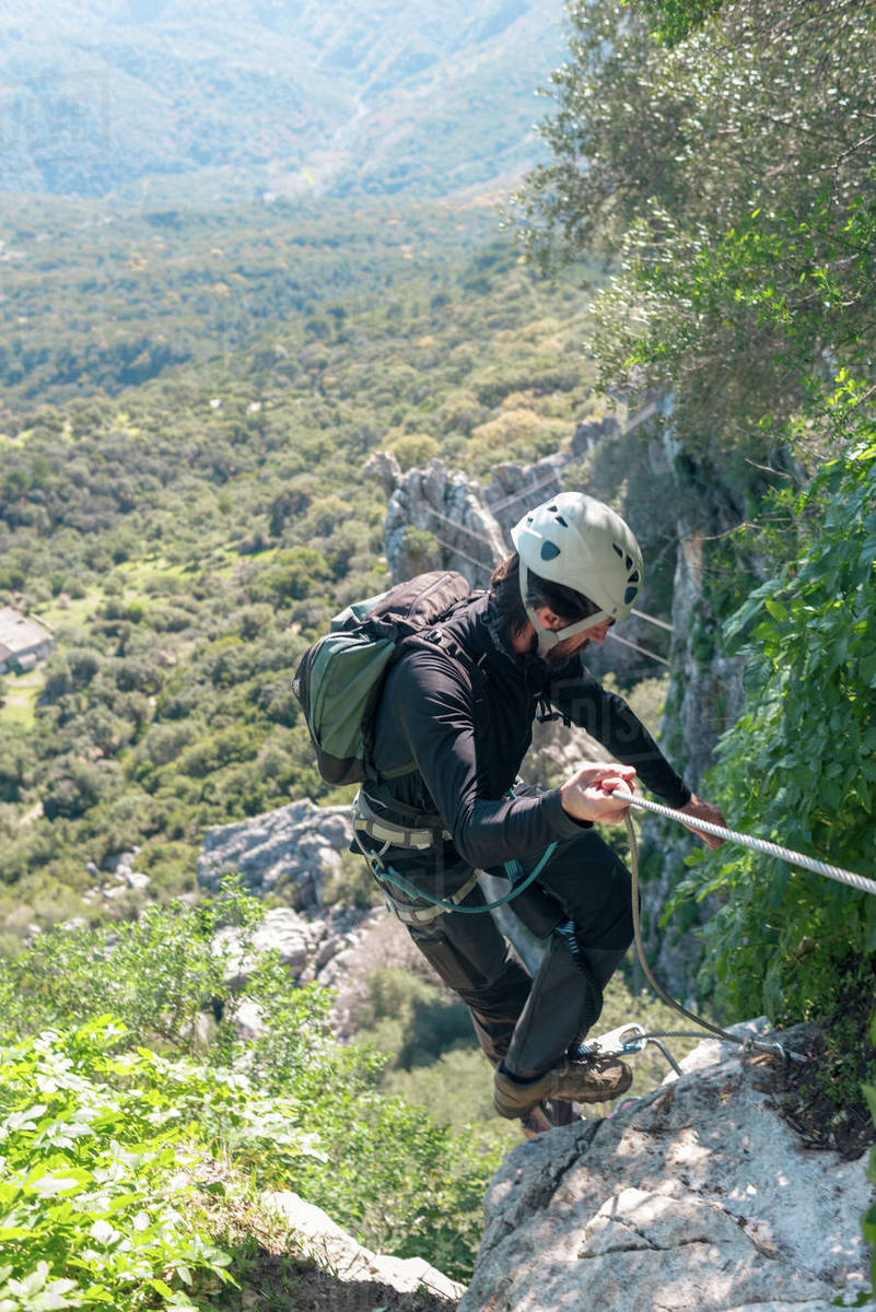 Adventure. Man with helmet, harness and backpack. Descending in the mountains by a via ferrata. Royalty-free stock photo