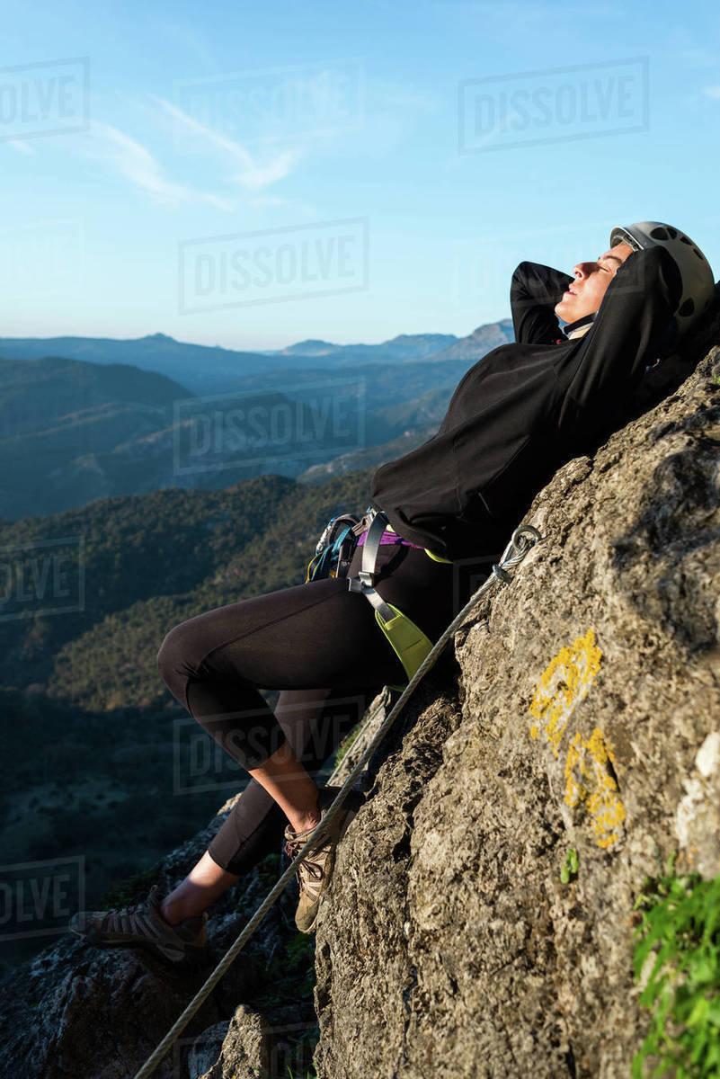 Concept: adventure. Climber woman with helmet and harness. Lying on a rock taking a sunbath. Via ferrata in the mountains. Royalty-free stock photo