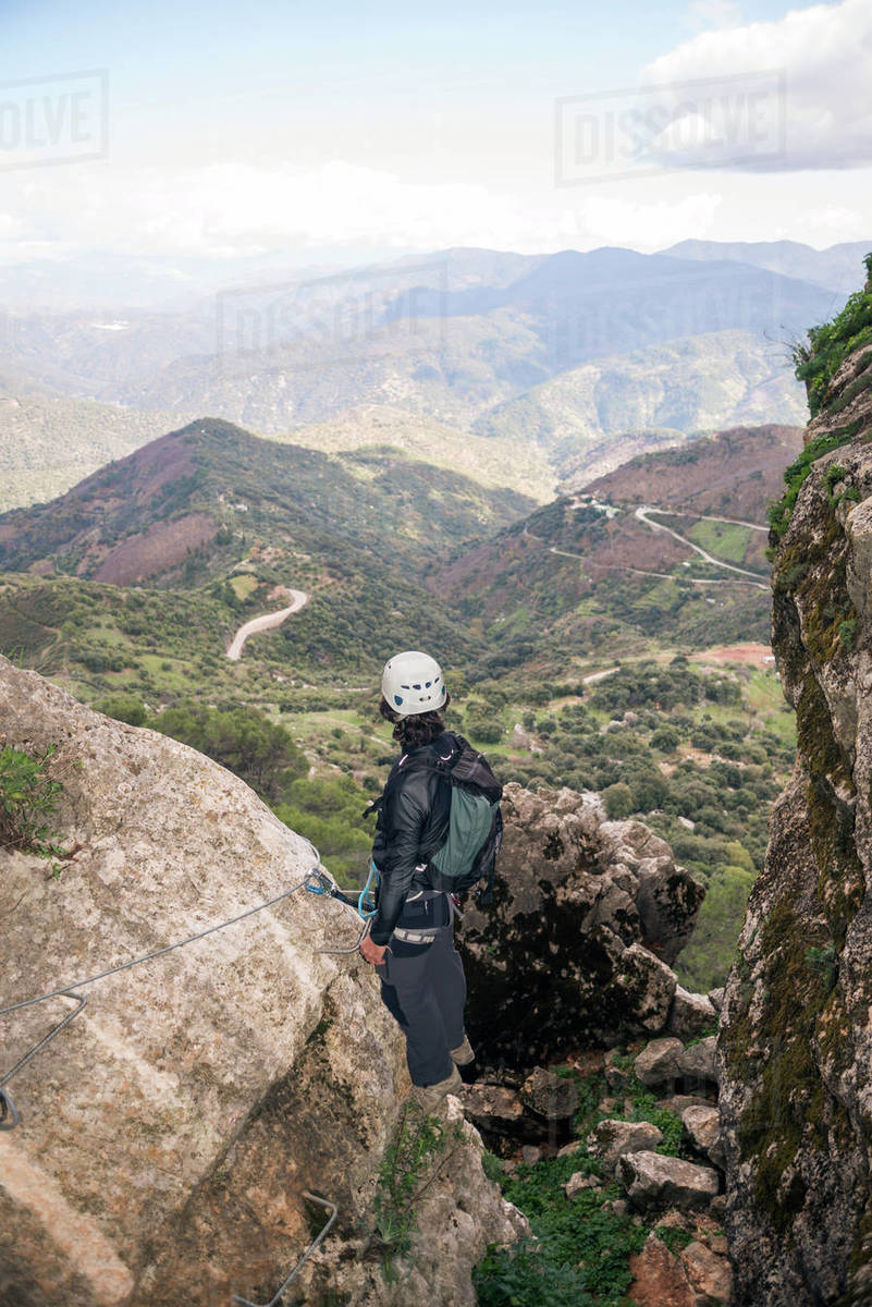 Concept: adventure. Climbers man with helmet and harness. From behind looking at the Andalusian natural landscape. Climbing to the top of the mountain. Via ferrata on rock. Royalty-free stock photo