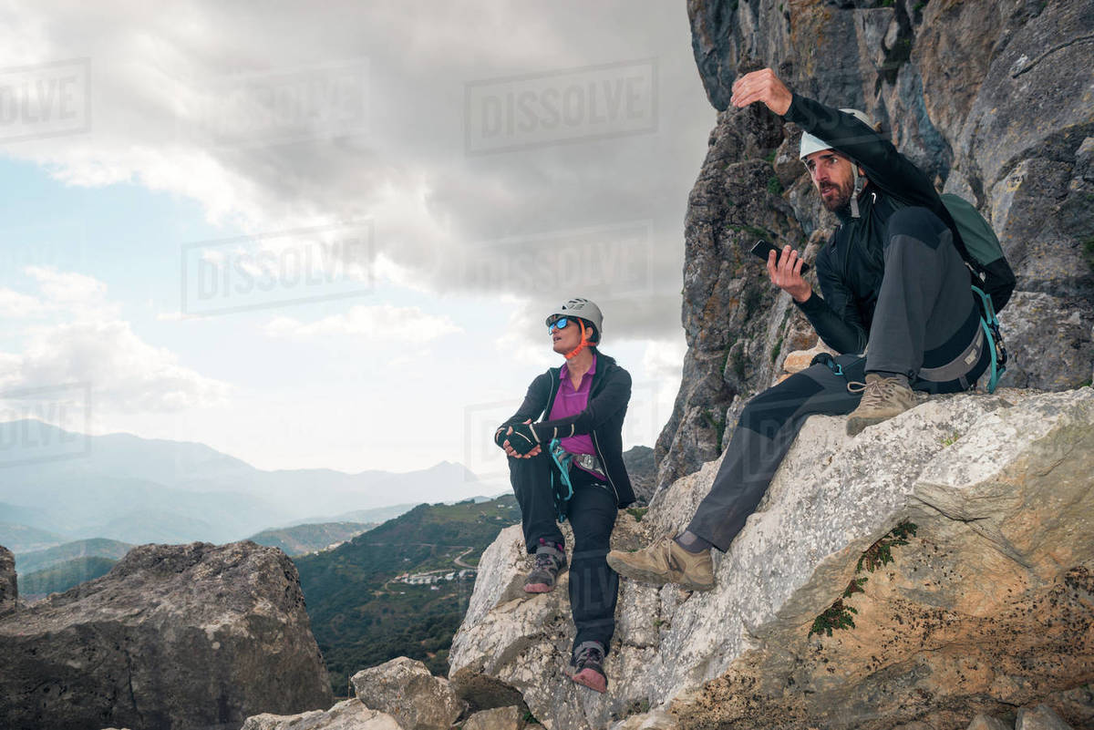 Concept: adventure. Man and woman climbers with helmet and harness. Resting sitting on a rock. Talking and gesturing while looking at the horizon. Via ferrata in the mountains. Royalty-free stock photo