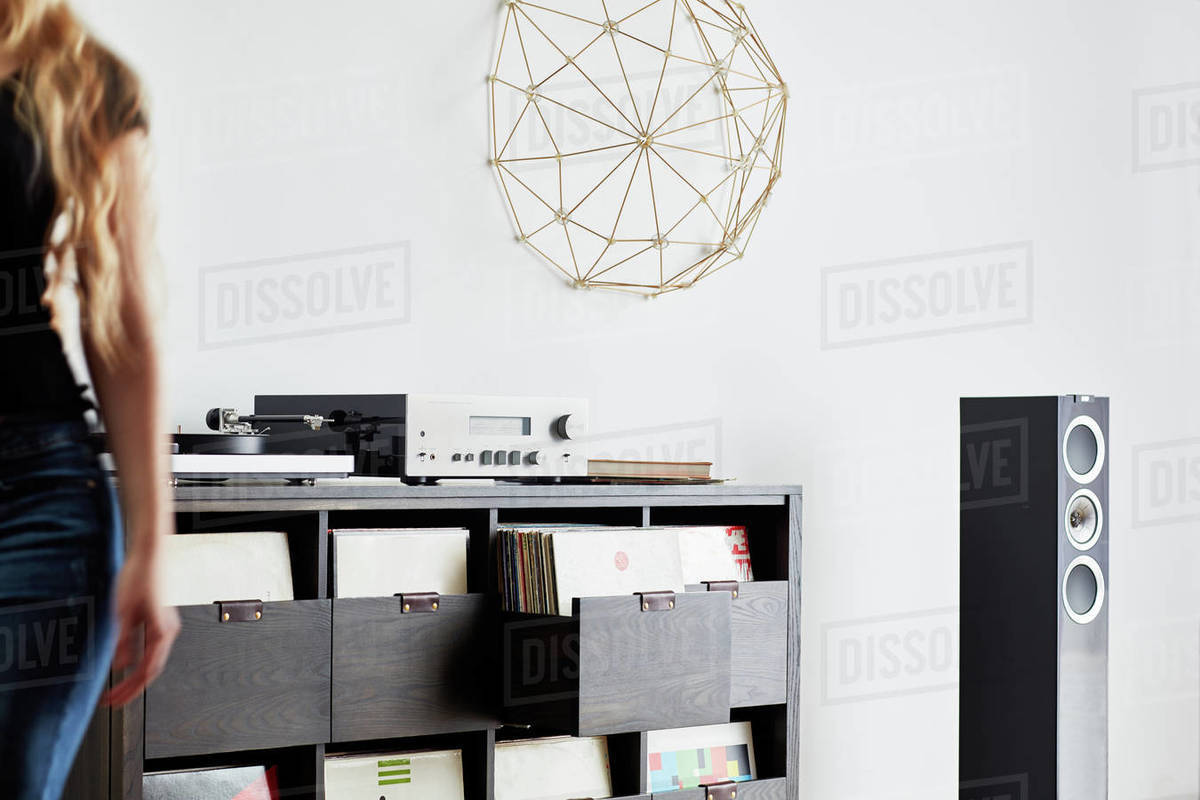 Woman and stereo cabinet and record collection Royalty-free stock photo