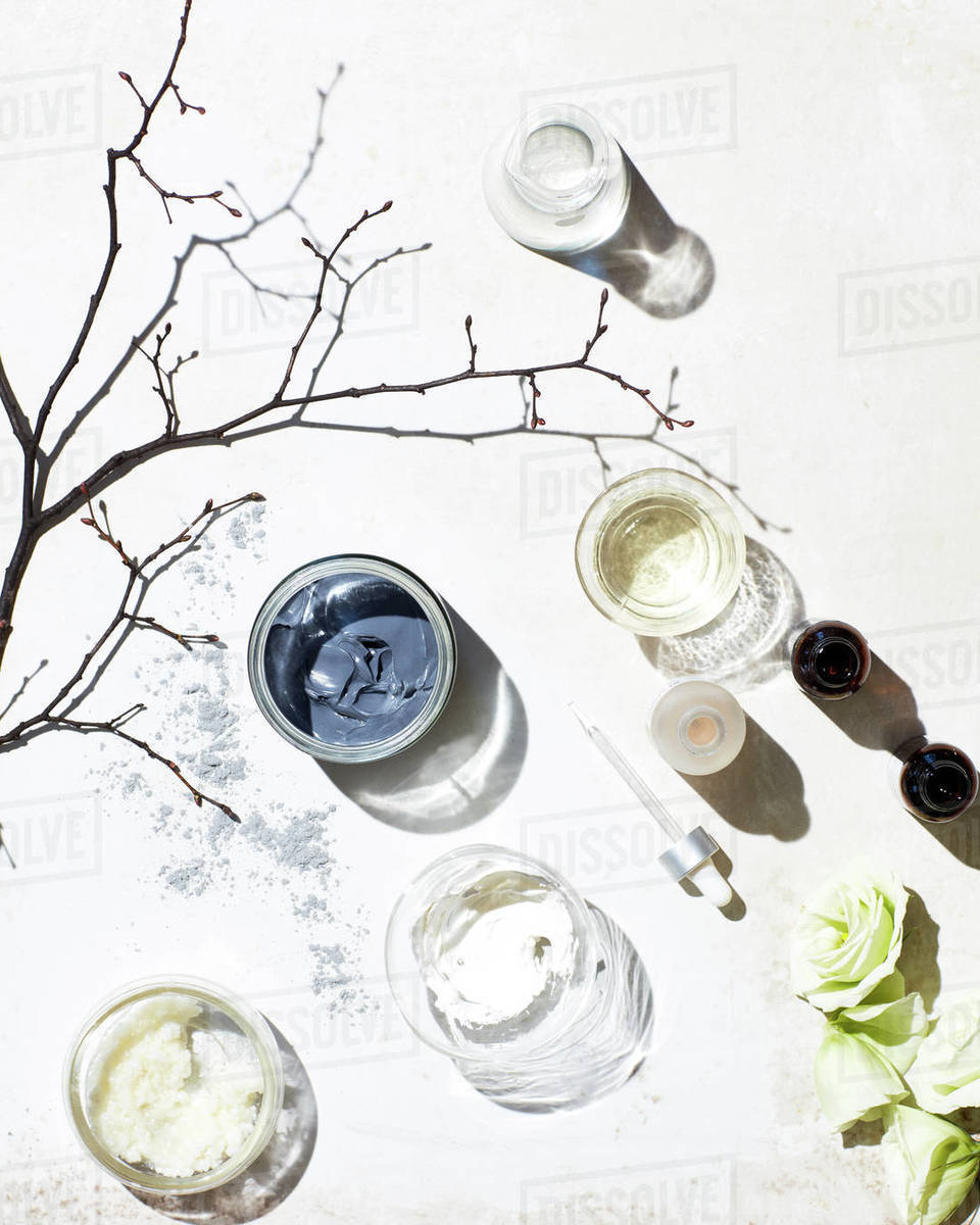 Skincare ingredients w/ branch, flowers on white surface Royalty-free stock photo