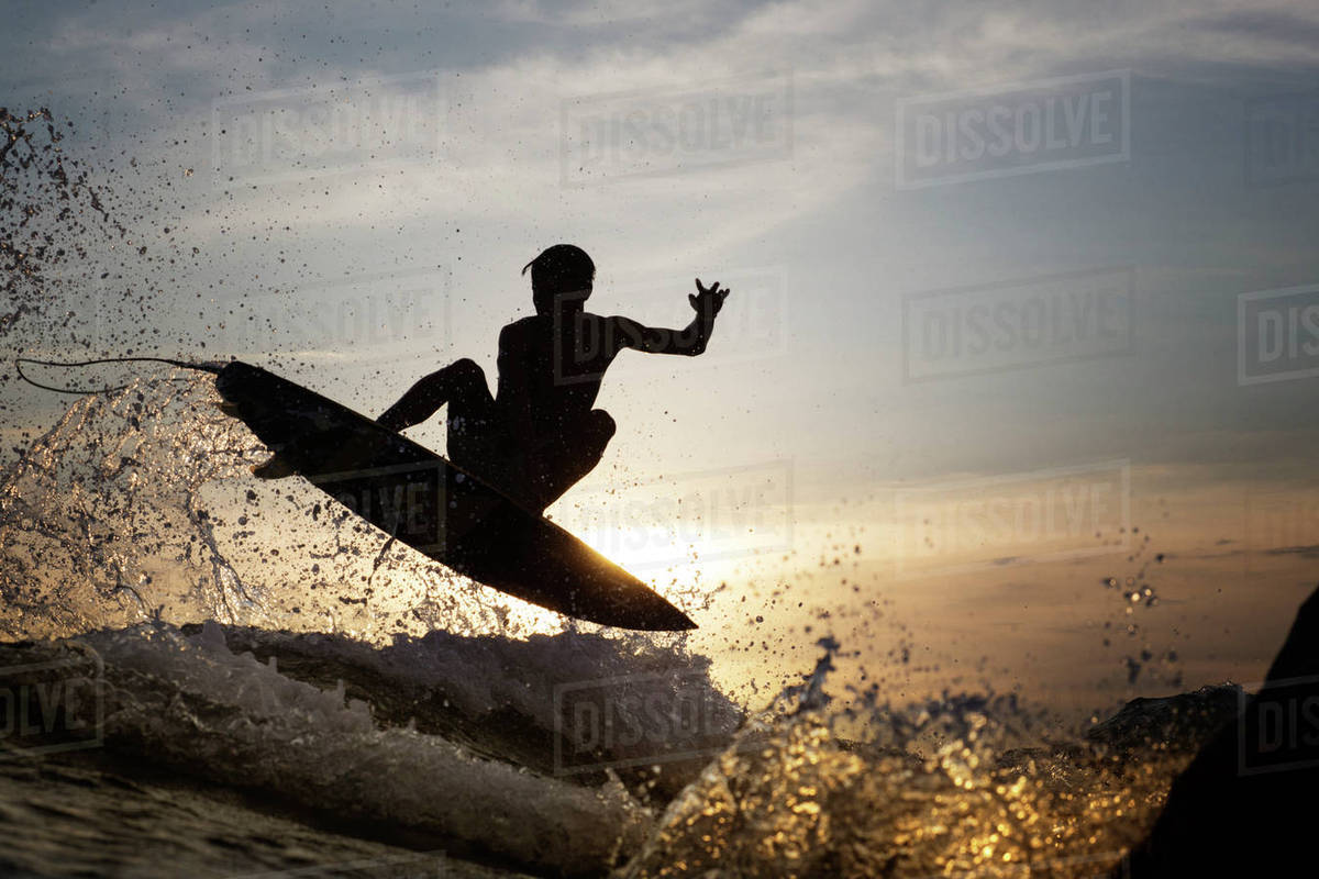 Young male surfer jumping over sea during sunset Royalty-free stock photo