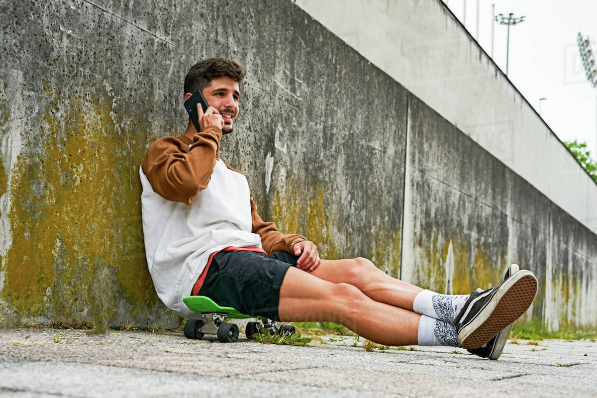 Young casual man sits outdoor on skateboard and uses phone Royalty-free stock photo