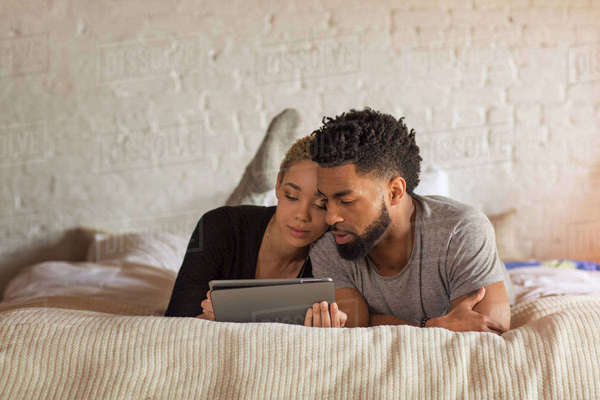 Multi-ethnic couple using tablet computer while lying on bed at home Royalty-free stock photo