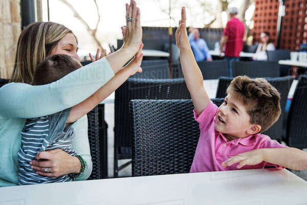 Mother and sons giving high-five at restaurant table Royalty-free stock photo