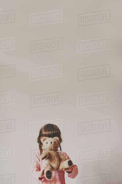 Girl holding teddy bear in front of face against white wall Royalty-free stock photo