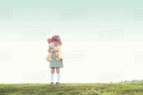Cute girl embracing doll while standing on field against clear sky Royalty-free stock photo