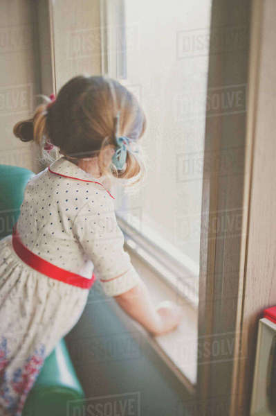 Side view of girl looking through window at home Royalty-free stock photo