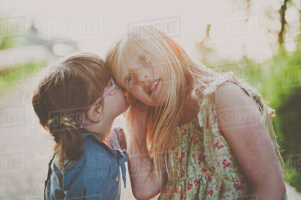 Side view of girl whispering into sister's ear on footpath Royalty-free stock photo