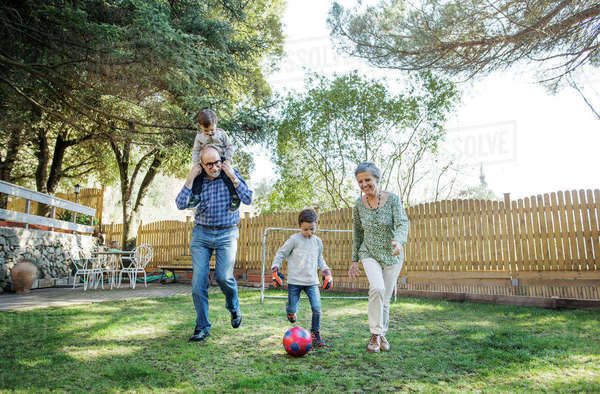Full length of grandparents and grandsons playing soccer at yard Royalty-free stock photo