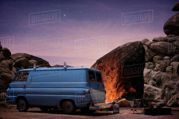 Van parked at campsite next to fire at dusk in Joshua Tree State Park Royalty-free stock photo