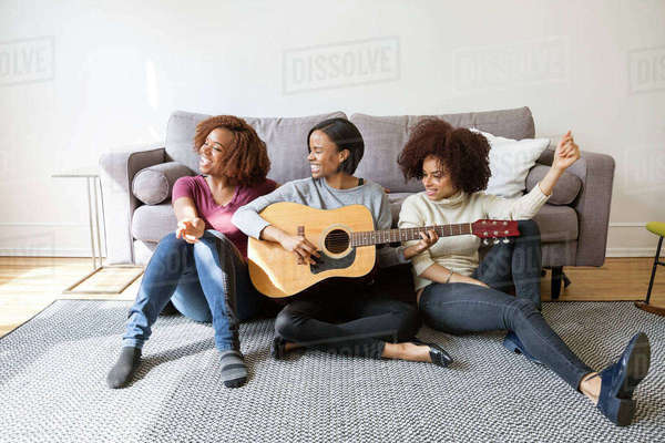 Cheerful woman playing guitar for female friends at home Royalty-free stock photo