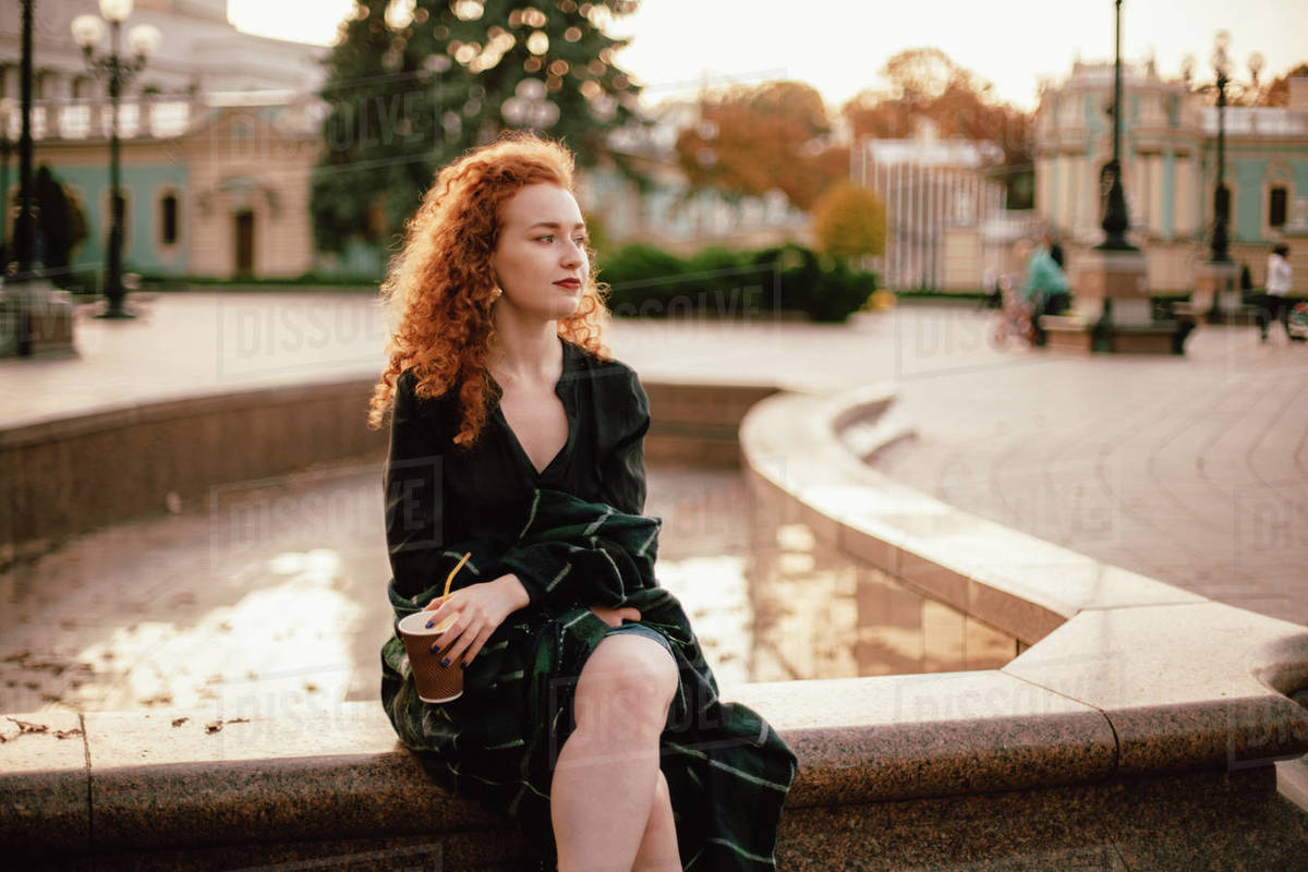 Young thoughtful red head woman sitting on fountain in city Royalty-free stock photo