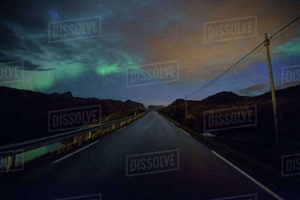 Aurora borealis over bridge and silhouette mountains Royalty-free stock photo