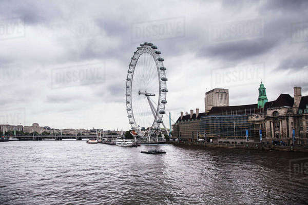 Millennium Wheel by Thames River against cloudy sky Royalty-free stock photo