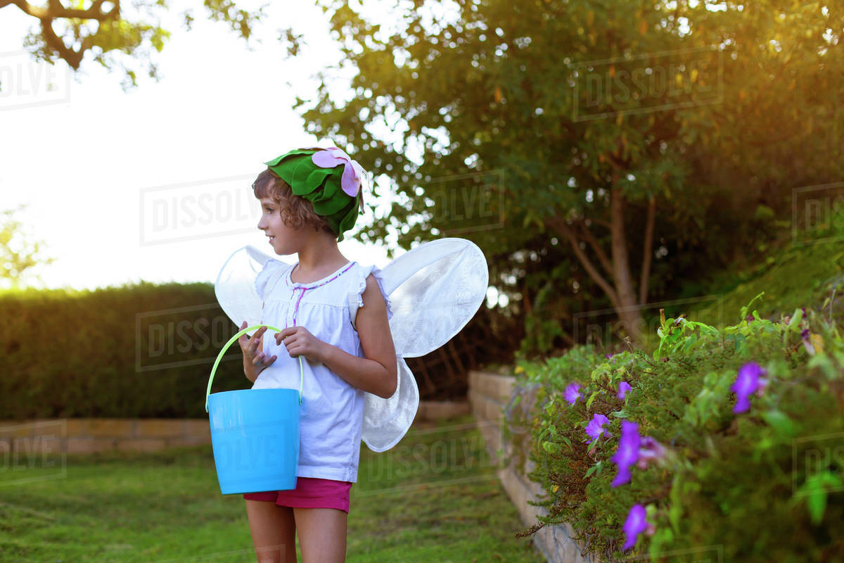 Girl (8-9) in butterfly costume holding bucket Royalty-free stock photo