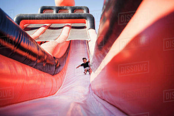 Boy (4-5) on red inflatable slide Royalty-free stock photo