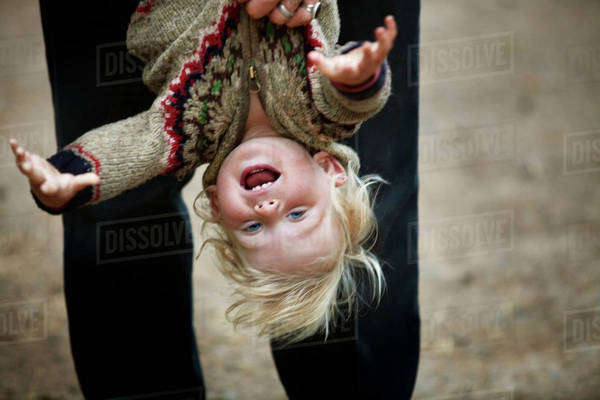 Smiling child (12-17 months) held upside down Royalty-free stock photo