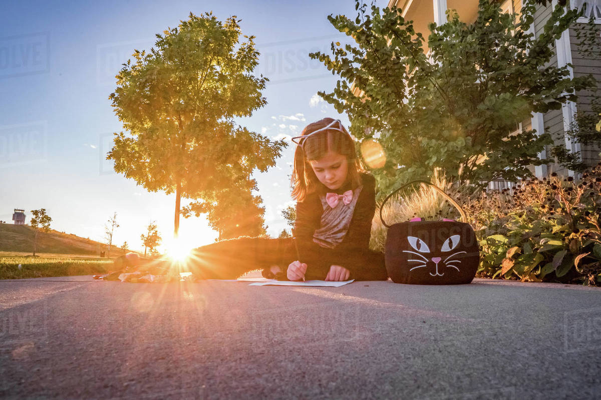Young girl in a cat costume writes a note near a cat Halloween bucket Royalty-free stock photo