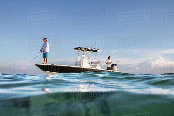 Low angle view of men fishing while standing on boat at sea against sky Royalty-free stock photo