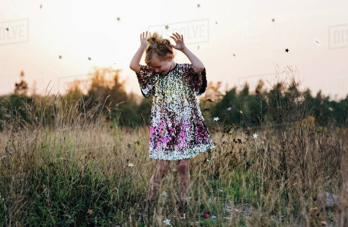 Little girl dancing in a sparkly dress with star confetti falling Royalty-free stock photo