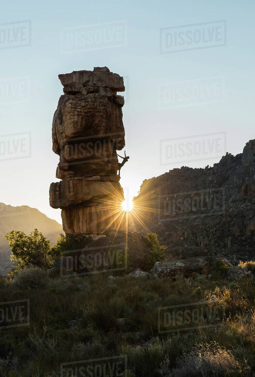 Athletic male climbs outside on a boulder with sun rays Royalty-free stock photo