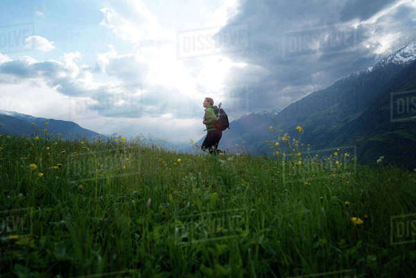 Side view of female hiker walking on field against cloudy sky Royalty-free stock photo