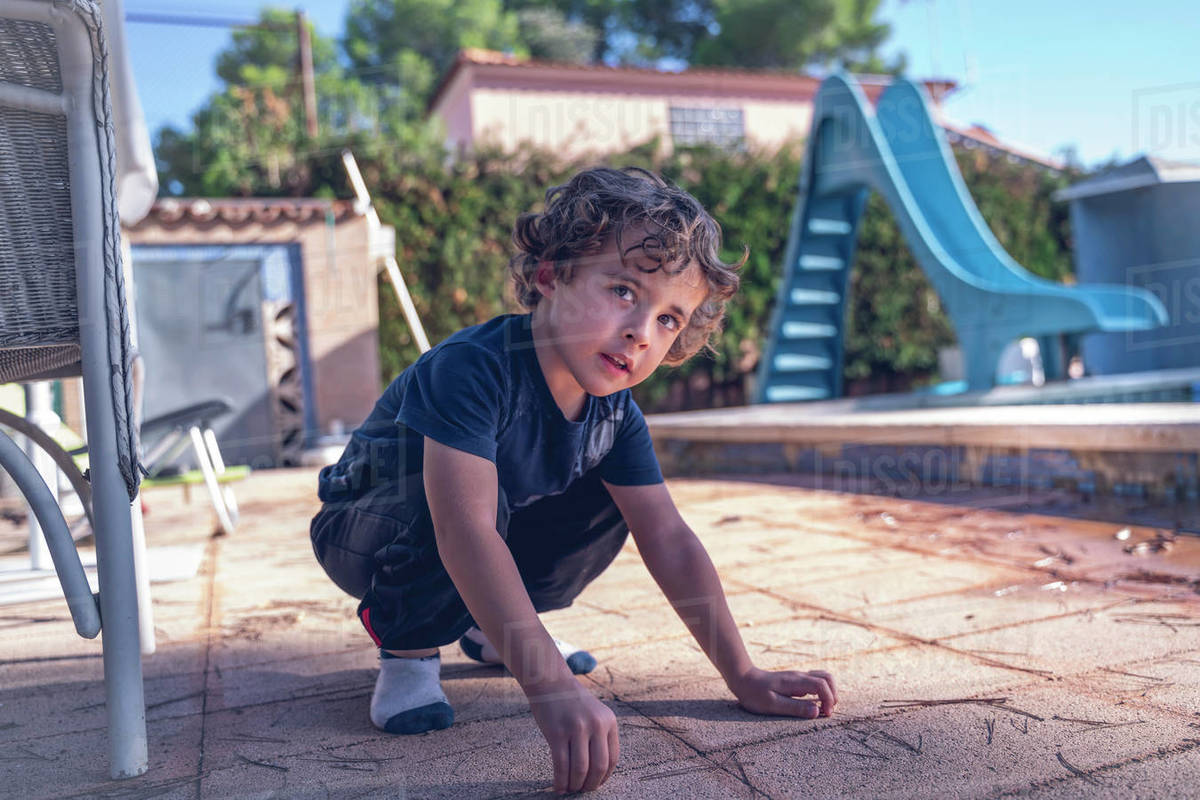 Very young boy of 4 years, he plays in the garden of a rural house. Royalty-free stock photo