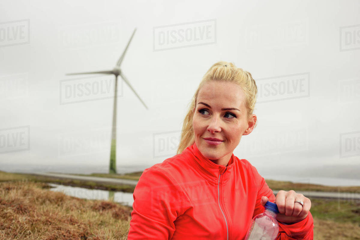 Sportswoman opening bottle of water in nature Royalty-free stock photo
