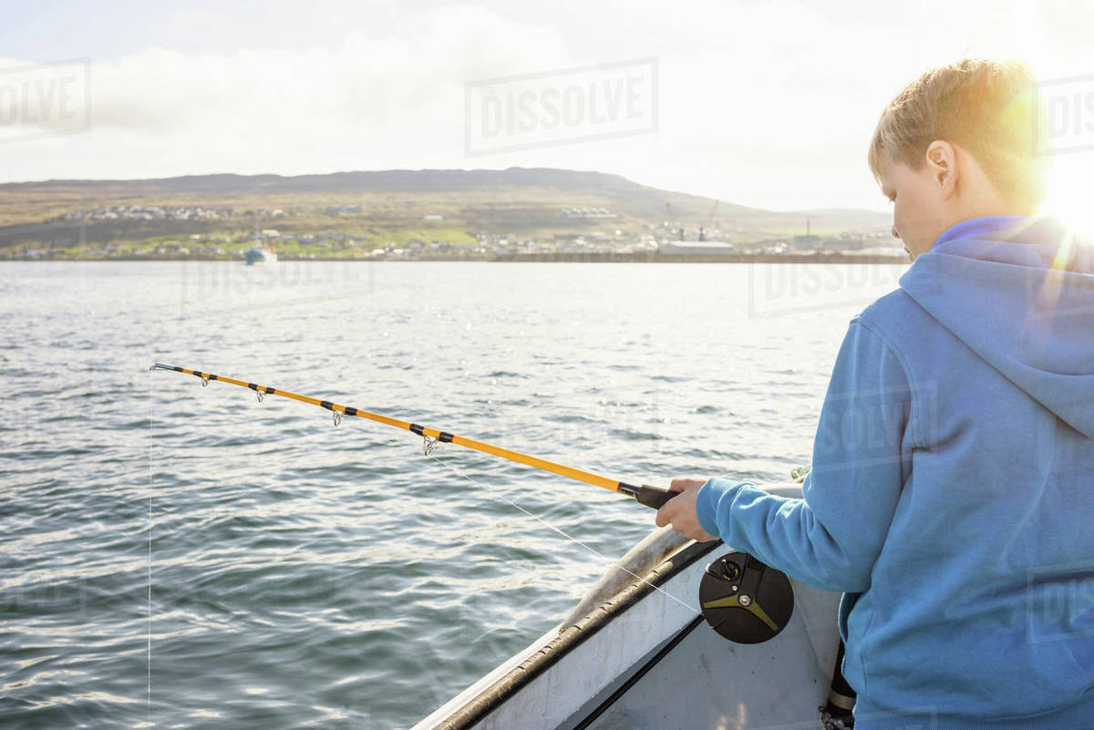 Teenager fishing with rod on boat Royalty-free stock photo
