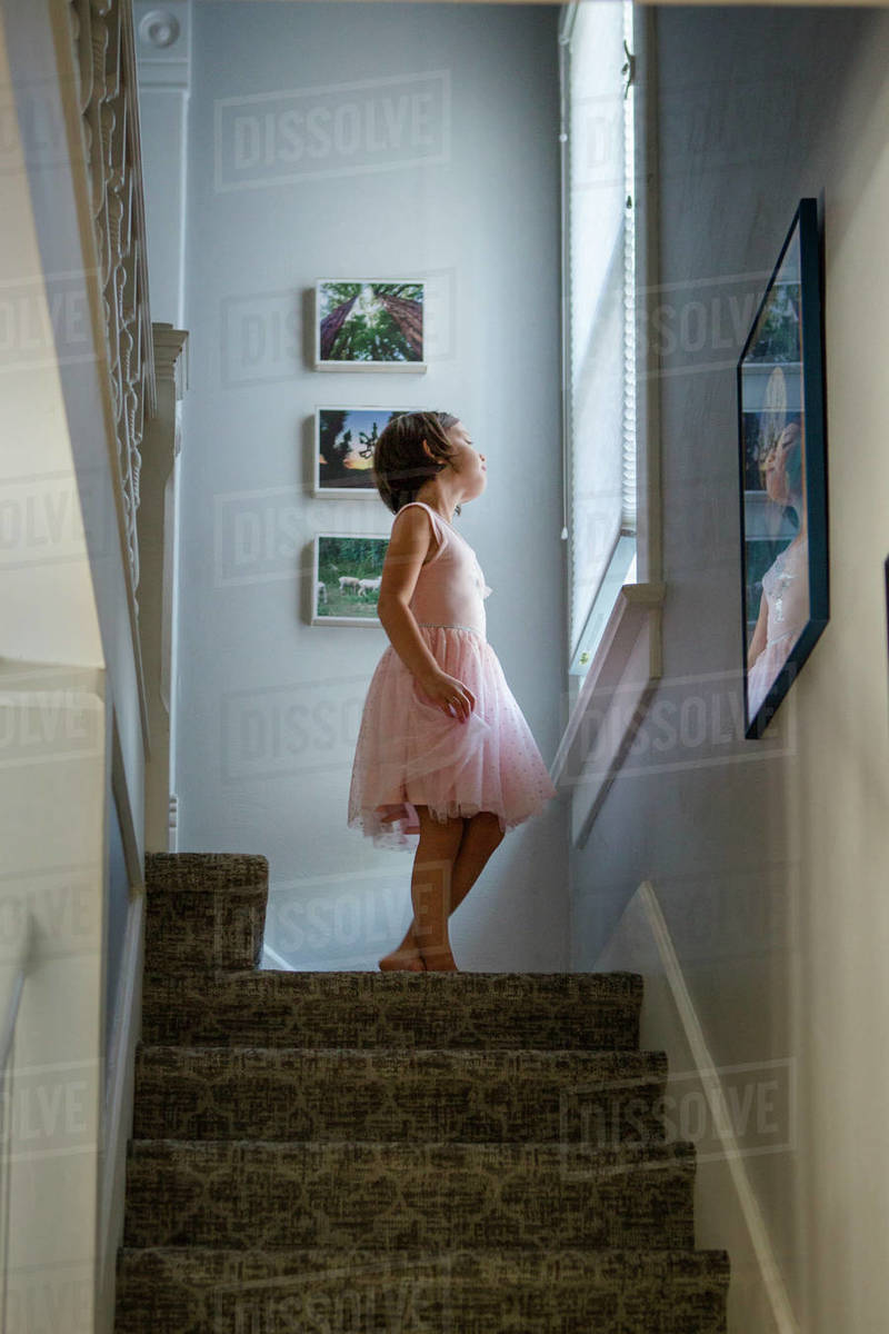 A small girl in dress stands at top of staircase gazing out the window Royalty-free stock photo