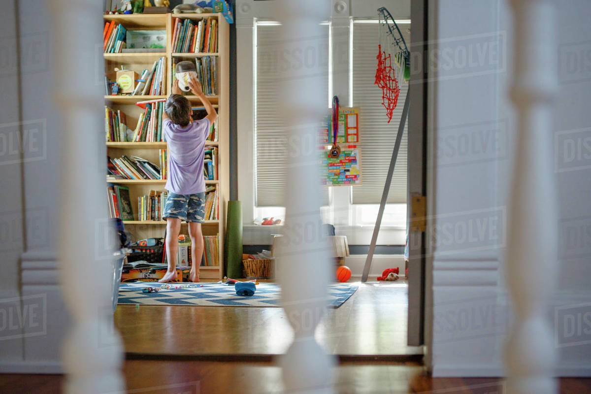 View through stair railing of a boy exploring a tall bedroom bookshelf Royalty-free stock photo