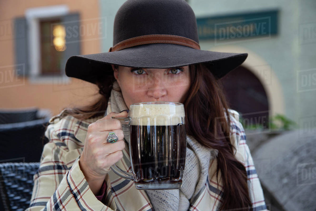 A young woman sipping beer foam at an outdoor restaurant in Germany Royalty-free stock photo