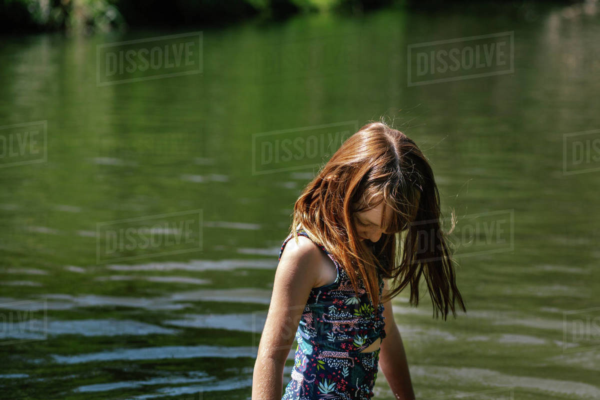 Portrait of young girl standing in a river on a sunny summer day Royalty-free stock photo
