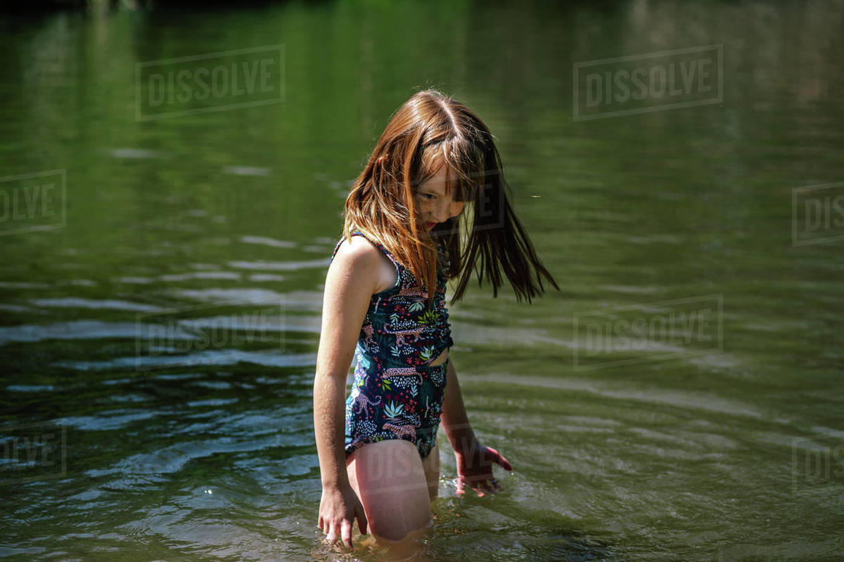 Portrait of a young happy girl playing in a river on a sunny day Royalty-free stock photo