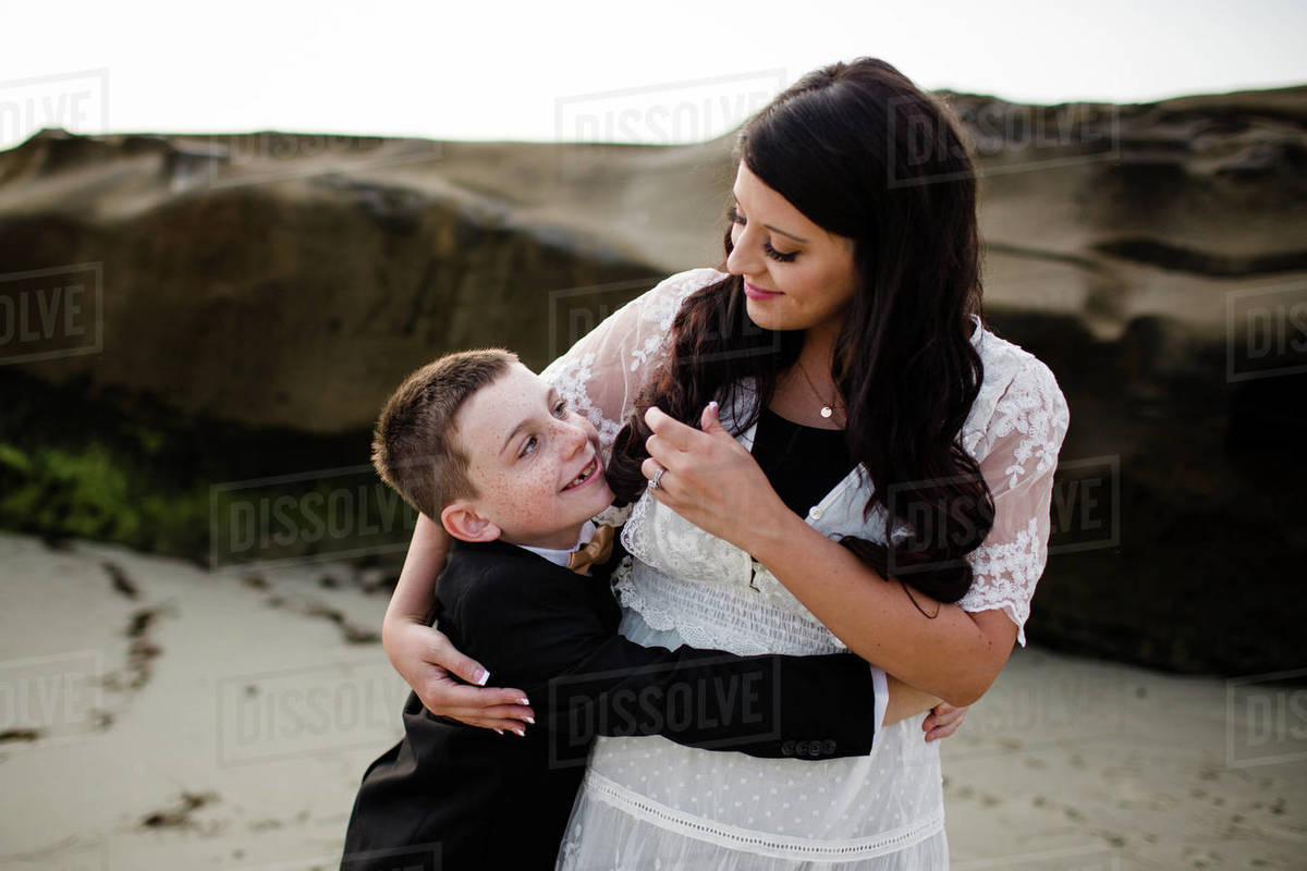 Newlywed Mother Embracing Son on Windansea Beach in San Diego Royalty-free stock photo