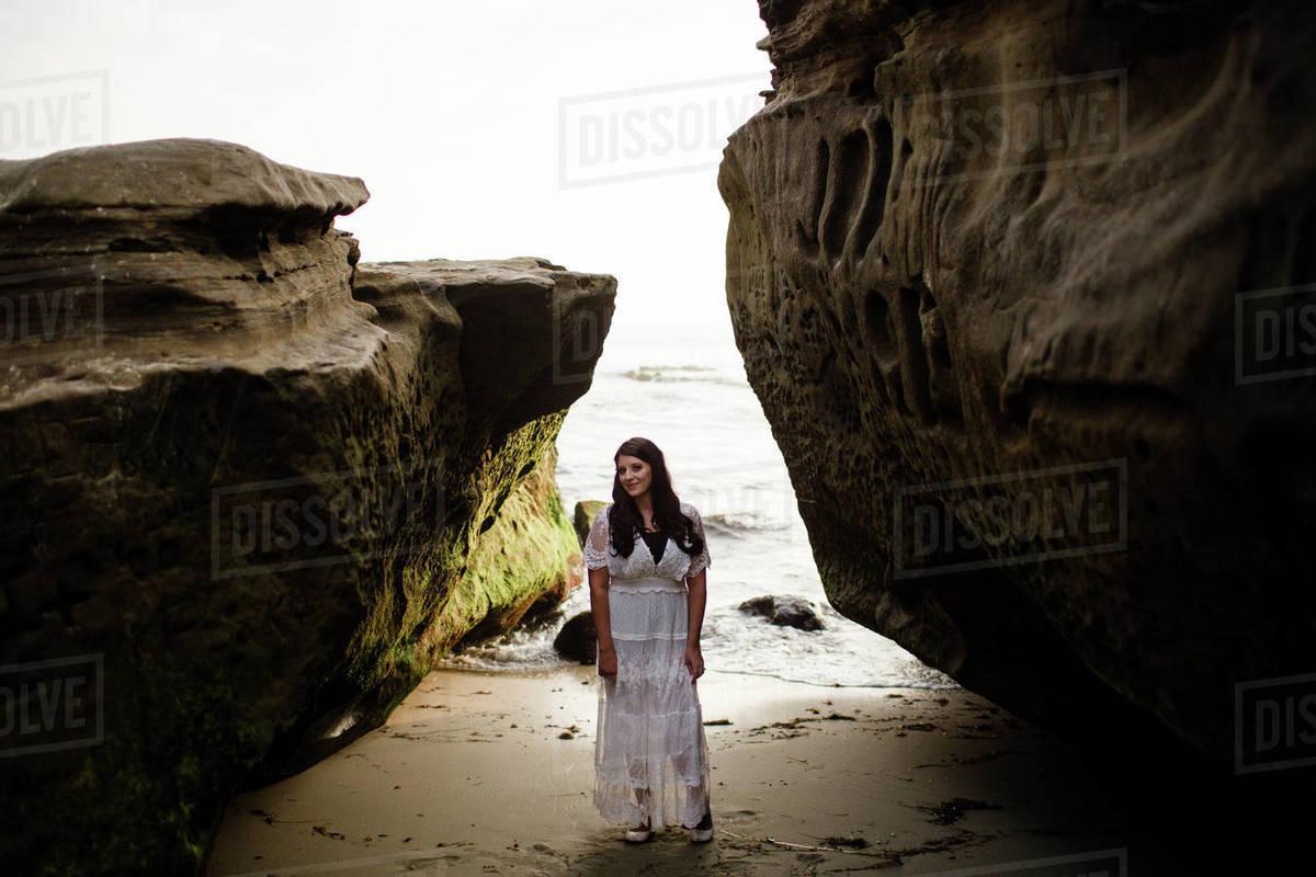 Newlywed Bride Standing Between Rocks on Beach in San Diego Royalty-free stock photo