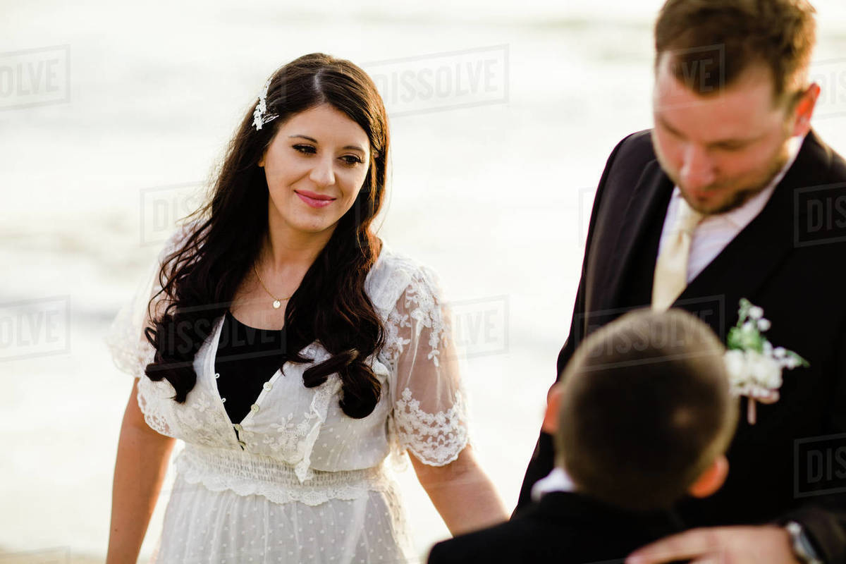 Mother Looking on at Husband & Son on Beach in San Diego Royalty-free stock photo