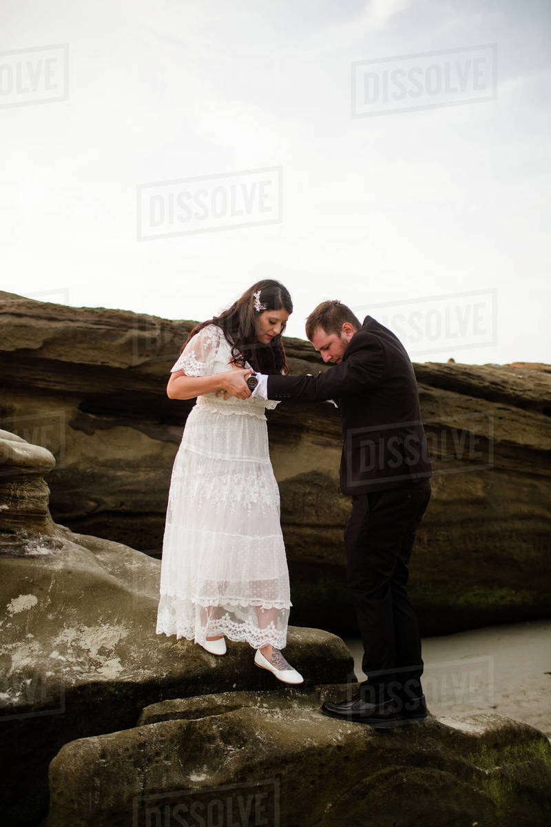 Newlyweds Climbing off of Rock on Beach in San Diego Royalty-free stock photo