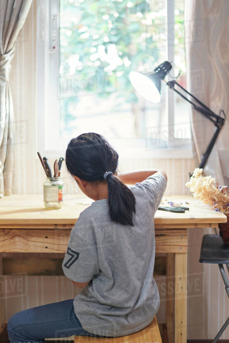 Rare view of a girl working on the wooden table Royalty-free stock photo