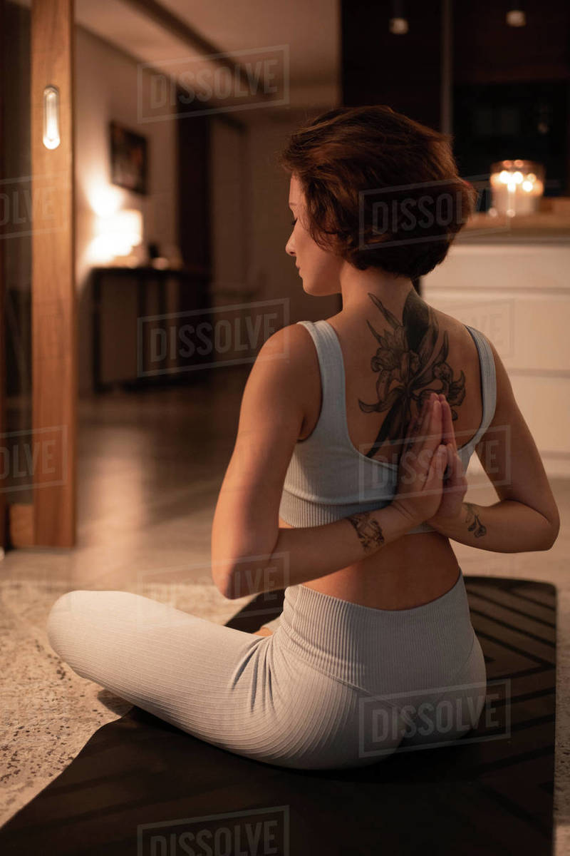 Woman meditating with hands clasped behind back Royalty-free stock photo