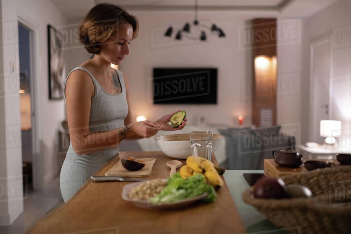 Young woman preparing avocado salad Royalty-free stock photo