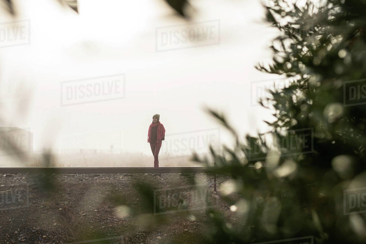 Thoughtful woman standing on a foggy railroad while looking away Royalty-free stock photo