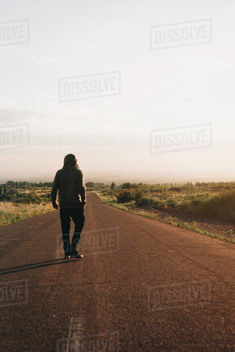 Young man walking on street at sunrise Royalty-free stock photo