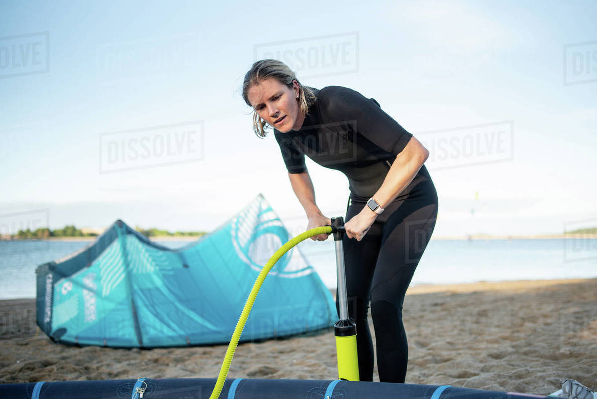 A woman in wetsuit pumps up a kiteboarding kite on a beach Royalty-free stock photo