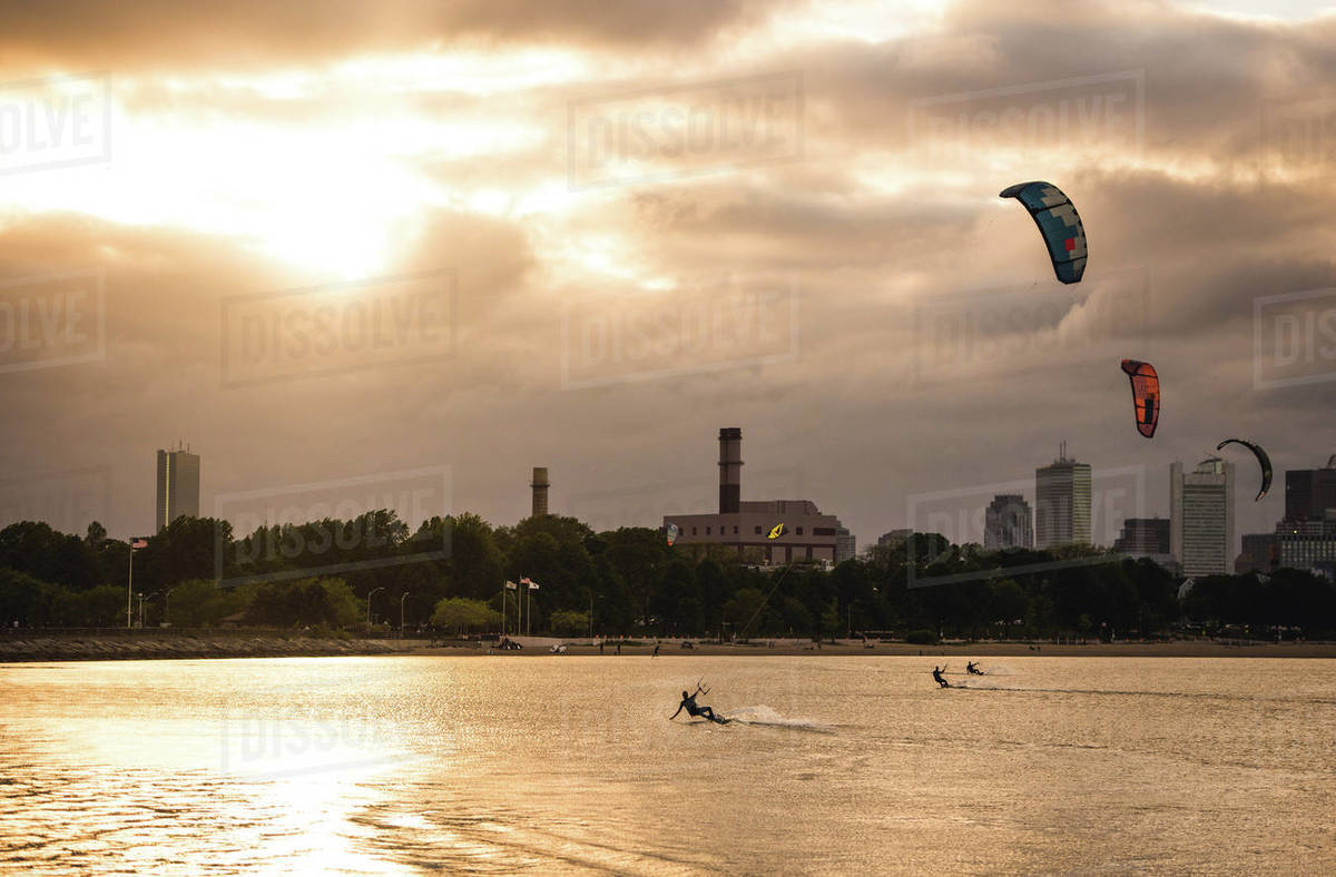 A woman kiteboarding on a summer evening with a cloudy Boston skyline Royalty-free stock photo
