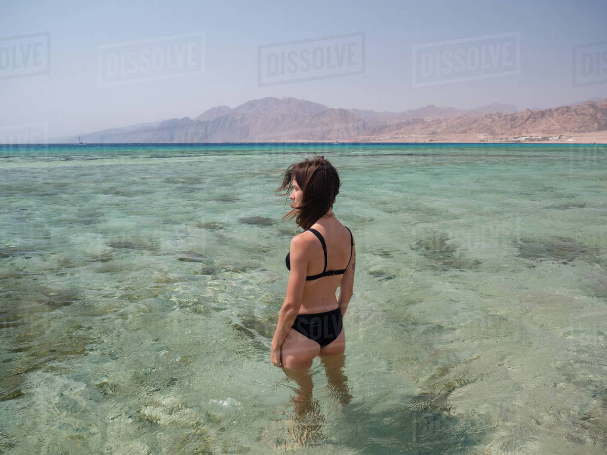 Young brunette woman relaxing in the sea with mountain backdrop Royalty-free stock photo